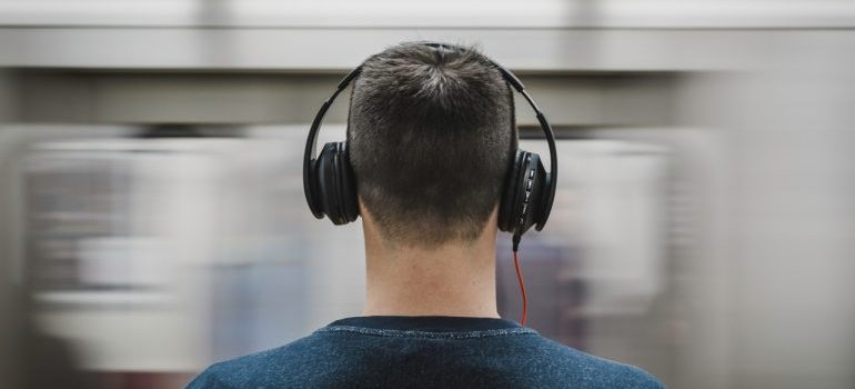 man wearing headphones next to a moving train