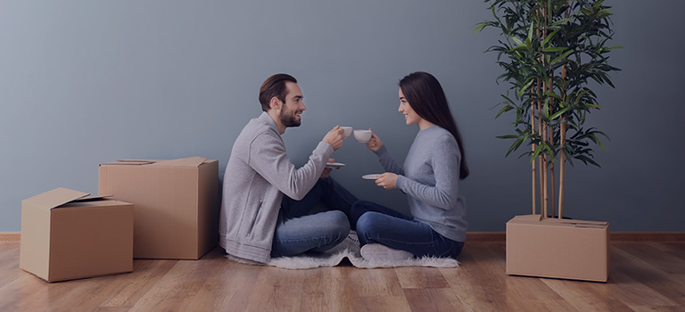 A couple, drinking coffee, surrounded by moving boxes.