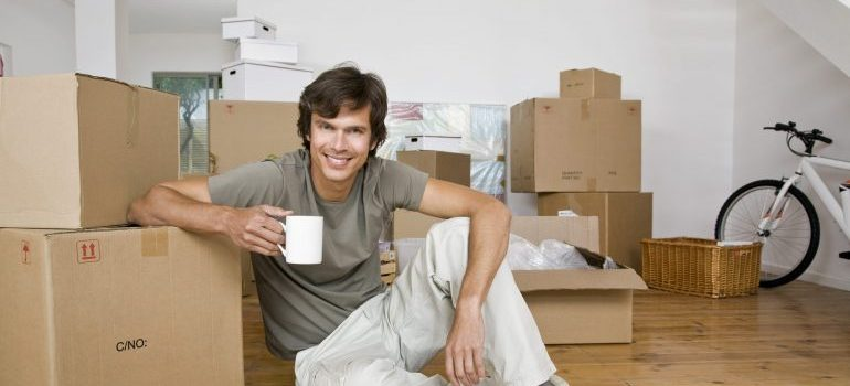 Man drinking coffee, surrounded by boxes - Zenith Moving handles the rest!