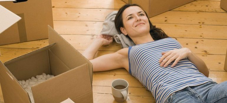 Woman surrounded by moving boxes, drinking coffee.