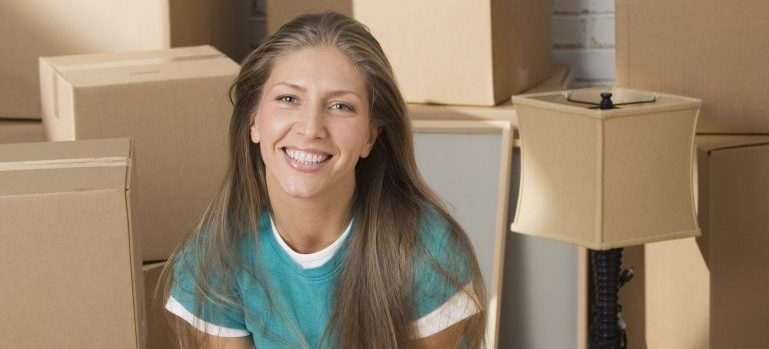 Woman smiling, surrounded by moving boxes.